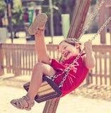 Criança de riso em dres vermelhos no balanço chain Fotografia de Stock
