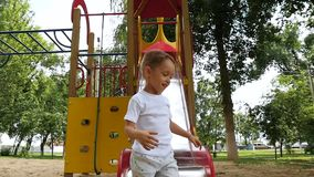 Criança de riso feliz que joga no campo de jogos, rolando para baixo uma corrediça alta em um dia ensolarado do verão no parque r vídeos de arquivo