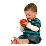 A criança de riso prende uma maçã vermelha Fotos de Stock Royalty Free