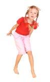 Criança de salto na camisa e em calças vermelhas. Imagem de Stock Royalty Free