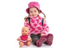 Criança de sorriso bonita e feliz que joga com seu brinquedo do bebê em um fundo branco foto de stock royalty free
