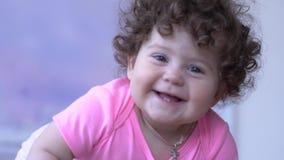 A criança de sorriso com cabelo encaracolado passa o tempo na sala em fundo unfocused filme