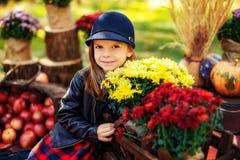 A criança de sorriso com a cesta das maçãs vermelhas que sentam-se no outono estaciona imagem de stock royalty free
