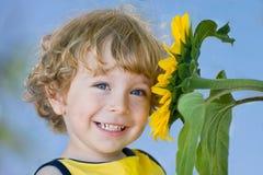 Criança de sorriso com girassol Foto de Stock Royalty Free