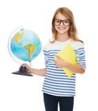 Criança de sorriso com globo, caderno e monóculos Fotos de Stock Royalty Free