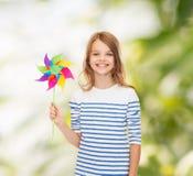 Criança de sorriso com o brinquedo colorido do moinho de vento fotografia de stock royalty free