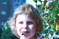 A criança de sorriso come bagas Fotografia de Stock Royalty Free
