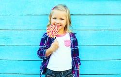 Criança de sorriso feliz bonito da menina com uma vara do pirulito fotografia de stock
