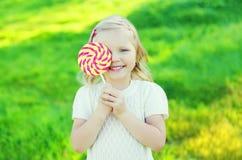 Criança de sorriso feliz com o pirulito doce do caramelo que tem o divertimento Imagens de Stock