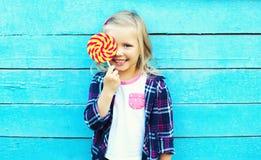 Criança de sorriso feliz com o pirulito doce que tem o divertimento Imagens de Stock Royalty Free