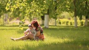 Criança de sorriso feliz da mãe e do filho que senta-se na grama e no jogo no dia de verão video estoque