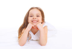 Criança de sorriso feliz da menina do retrato que encontra-se no branco fotografia de stock