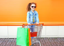Criança de sorriso feliz da menina no carro do trole com sacos de compras Imagem de Stock