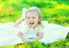 Criança de sorriso feliz da menina que encontra-se na grama no verão ensolarado Imagens de Stock