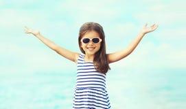 Criança de sorriso feliz do close-up do retrato do verão que levanta as mãos acima de ter o divertimento foto de stock royalty free