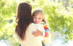 Criança de sorriso feliz do retrato que abraça a mãe no verão Fotos de Stock Royalty Free