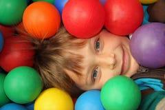 Criança de sorriso feliz que joga em esferas coloridas Fotografia de Stock Royalty Free