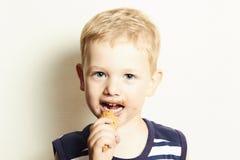 Criança de sorriso. menino bonito da criança que come o gelado Fotos de Stock Royalty Free