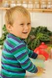 Criança de sorriso na cozinha Fotografia de Stock Royalty Free