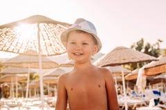 Criança de sorriso na praia em um counterlight do por do sol imagem de stock