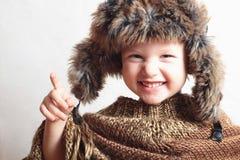 Criança de sorriso no chapéu forrado a pele estilo do inverno da forma Menino engraçado pequeno Emoção das crianças Foto de Stock