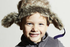 Criança de sorriso no chapéu forrado a pele estilo ocasional do inverno da forma Menino engraçado pequeno Emoção das crianças Imagens de Stock Royalty Free