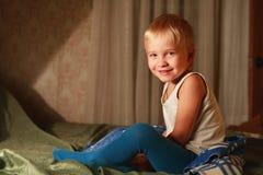 Criança de sorriso no quarto dos pais Foto de Stock Royalty Free