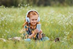 criança de sorriso nos fones de ouvido usando o smartphone ao descansar na cobertura no prado fotos de stock