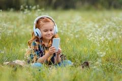 criança de sorriso nos fones de ouvido usando o smartphone ao descansar na cobertura no prado fotografia de stock