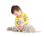 Criança de sorriso que abraça um filhote de cachorro fotografia de stock royalty free