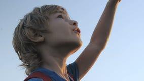 Criança de sorriso que olha o céu azul filme