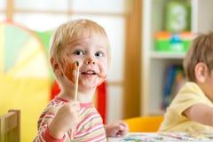 Criança de sorriso que pinta em casa Fotografia de Stock