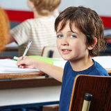 Criança de sorriso que senta-se na tabela foto de stock royalty free