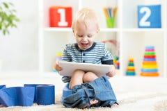 Criança de sorriso que senta-se no potenciômetro de câmara com toalete imagens de stock royalty free