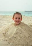 A criança de sorriso senta em um montão da areia em uma praia atrás dela o mar Fotos de Stock