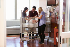 Criança de Visiting Parents And do pediatra na cama de hospital imagens de stock
