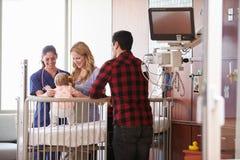 Criança de Visiting Parents And do pediatra na cama de hospital fotografia de stock royalty free