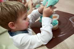 A criança decora queques Fotografia de Stock