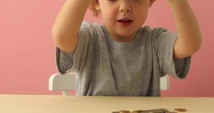 A criança derrama moedas do mealheiro