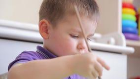 A criança diligente tira com pinturas coloridas ao sentar-se na tabela vídeos de arquivo