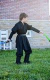 Criança disfarçada no traje de Star Wars: Darth Vader com espadas imagem de stock royalty free