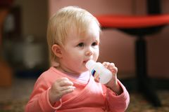 A criança do bebê come vitaminas ou comprimidos em casa imagens de stock royalty free