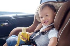 A criança do bebê da criança que senta-se na terra arrendada do carseat da segurança & aprecia comer a banana Fotos de Stock Royalty Free