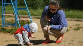 Criança do bebê de um ano que joga com a areia no campo de jogos Perto da mãe ajuda-o com o jogo Menino no waistcoat vermelho vídeos de arquivo