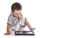 Criança do bebê que olha feliz em uma tabuleta digital Fotos de Stock