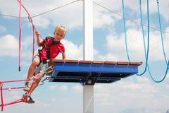 Criança do cabelo louro que joga o curso da corda exterior