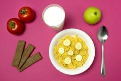 Criança do café da manhã na escola, flocos de milho com leite, maçã, pão no fundo cor-de-rosa foto de stock