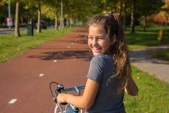 A criança do ciclista ou a menina do adolescente apreciam o bom tempo e o ciclismo imagem de stock royalty free