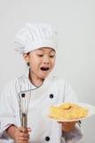 A criança do cozinheiro chefe, meninas veste trajes do cozinheiro chefe e guarda uma placa do alimento Fotos de Stock