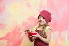 Criança do cozinheiro chefe no chapéu do cozinheiro, nas cookies da posse do avental ou nos biscoitos Foto de Stock